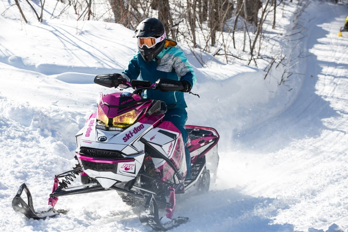 Snowmobiler riding uphill on a trail on a white and purple sled