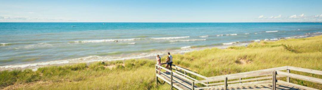 Un homme et une femme se tiennent au sommet d'un point de vue, regardant les vagues de la plage bleue