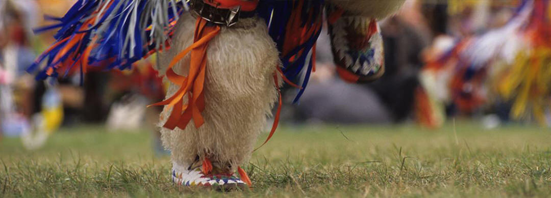 Close up view of an Indigenous dancer's feet at a Pow Wow, adorned in colourful traditional attire