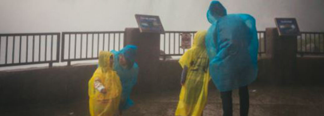 A group of people in rain poncho standing in front of the railing, while mist from Niagara Falls sprays