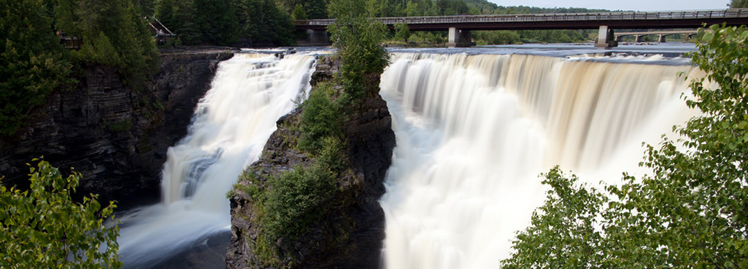 Water rushes down the falls with a low bridge in the background