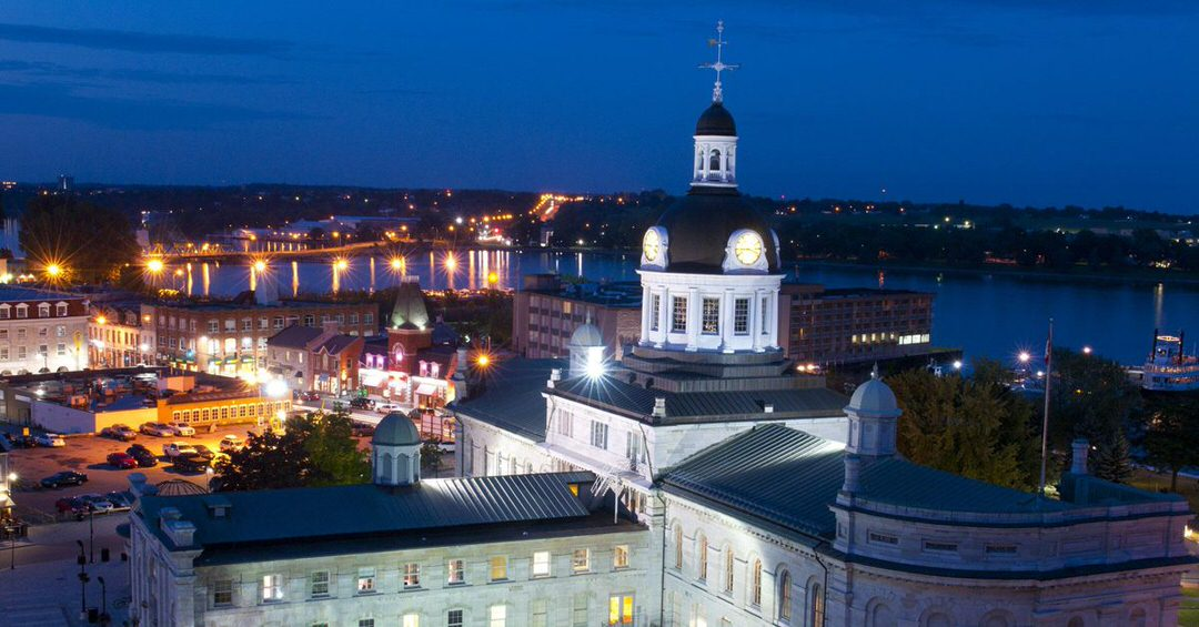 Historic buildings by the waterfront are lit by street lights during the evening.