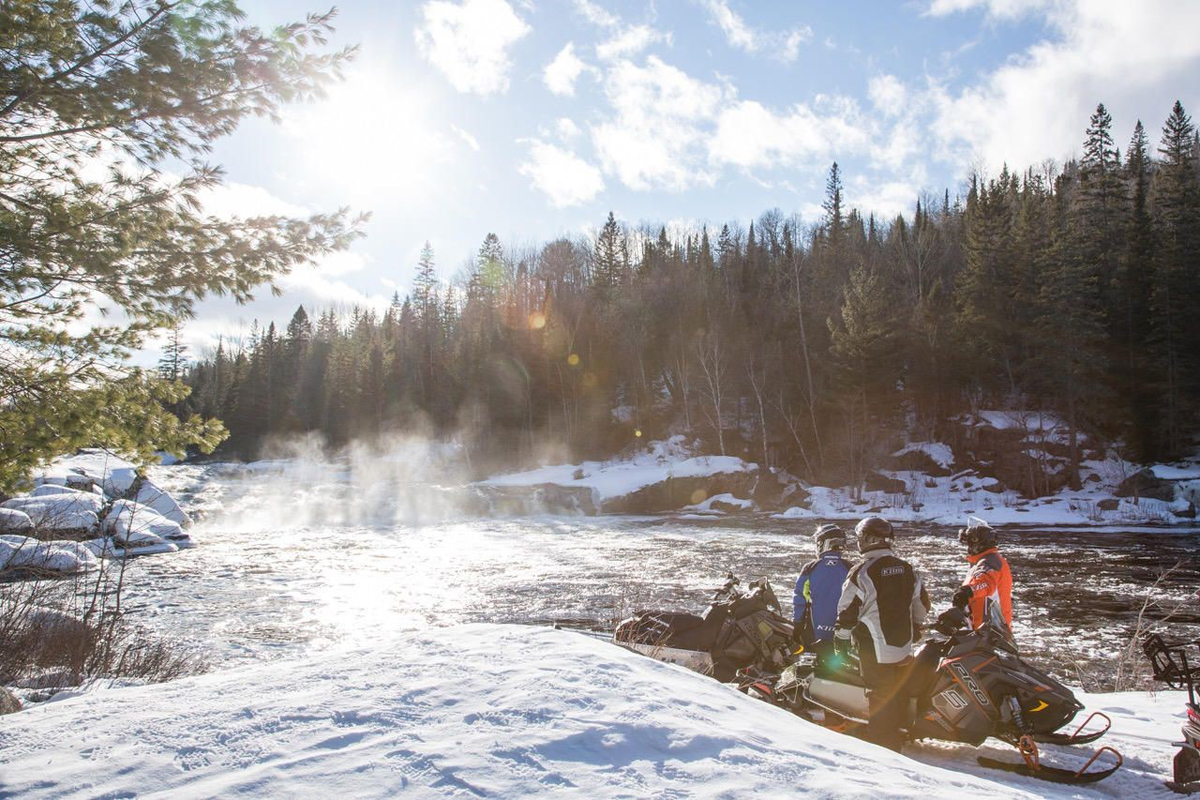 Three snowmobilers standing next to their sleds on a trail overlooking a scenic rushing river