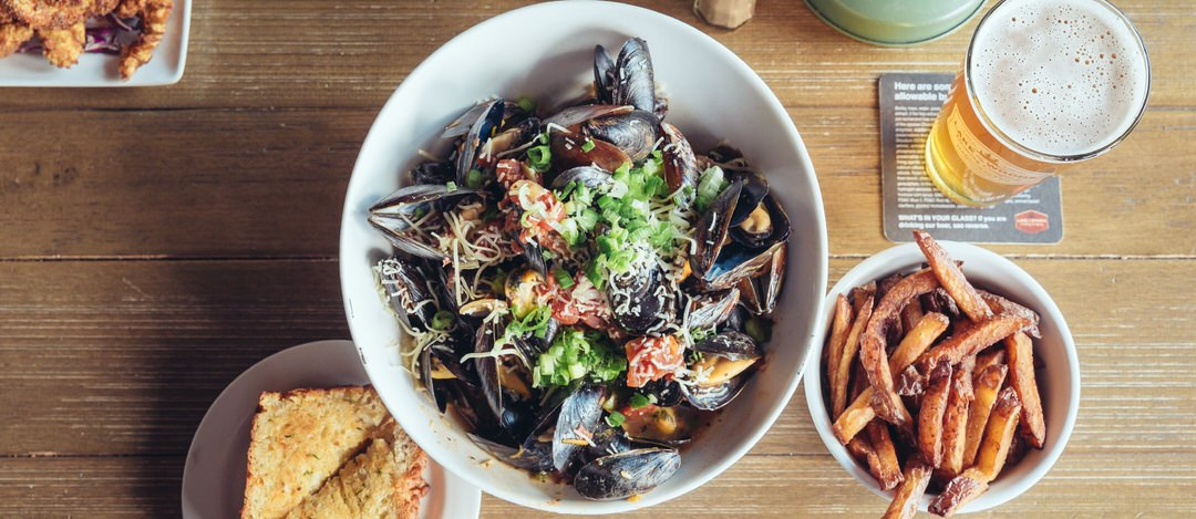 A large round bowl full of mussels, vegetables and shredded cheese, with a side of fries, garlic bread, breaded shrimp and a full glass of amber beer