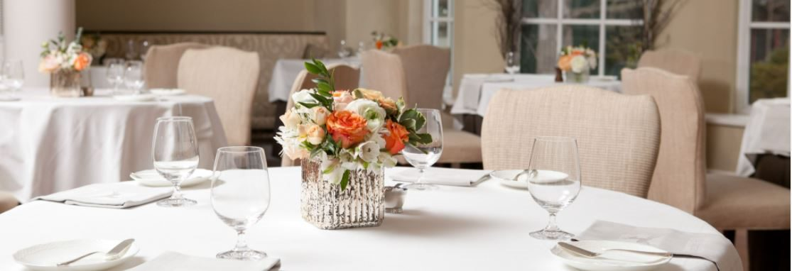 Langdon Hall Dining Room, chairs around round tables with white linen, decorated with flower center pieces