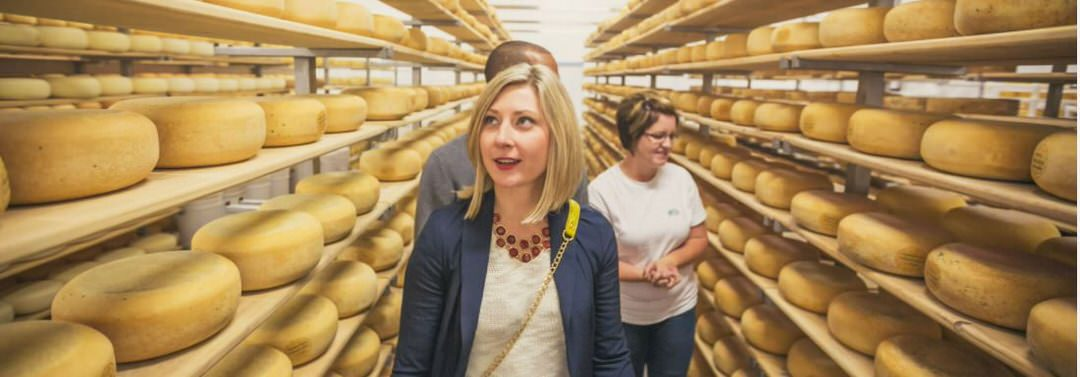 People taking a tour, walking through an isle with shelves full of large round cheese