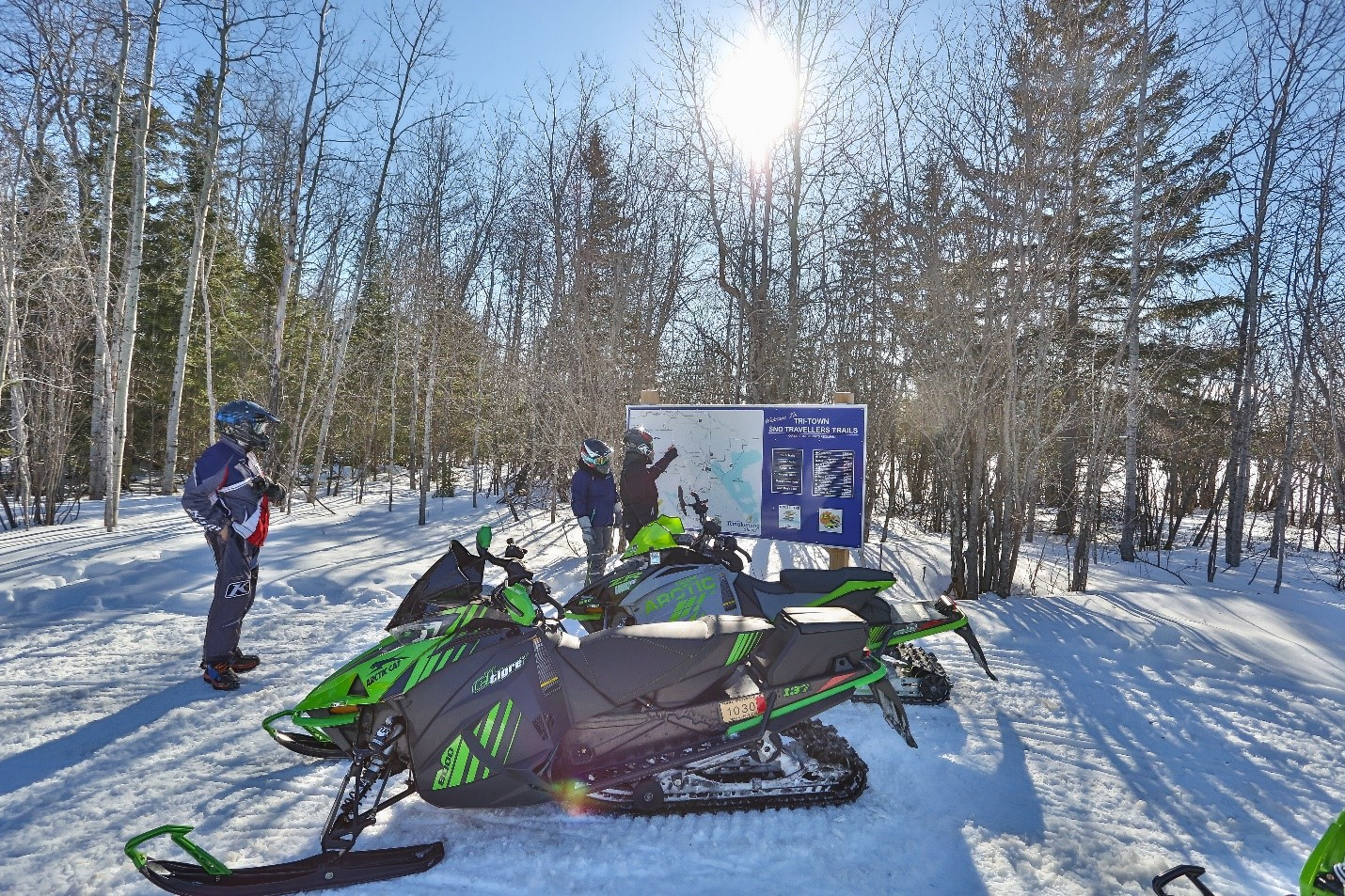 A group of three snowmobilers looking at an outdoor trail map on a sunny day