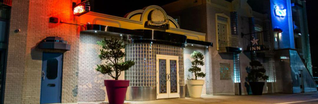 La façade avant de style rétro avec de grands planteurs d'arbres de chaque côté de la porte