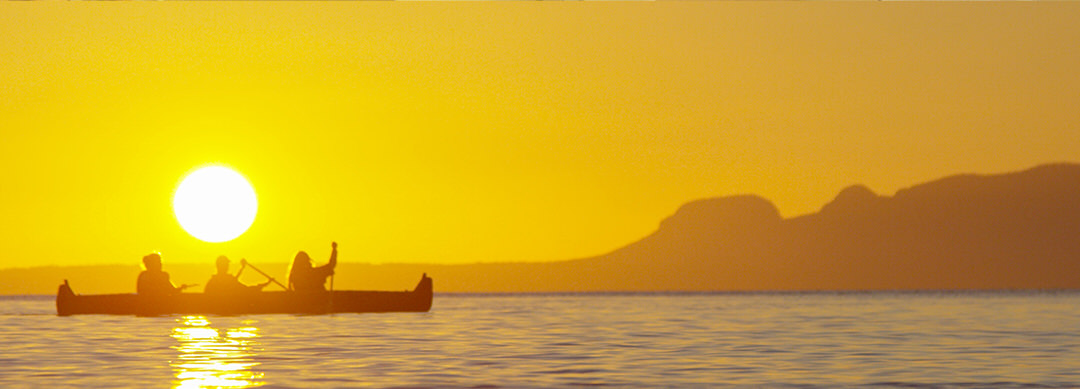 Three people canoe across the lake with the sleeping giant outlined against the bright yellow sunset in the background
