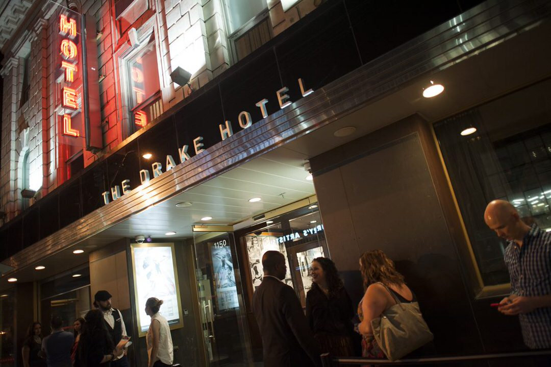 People hanging out in front of the Drake Hotel in the evening.