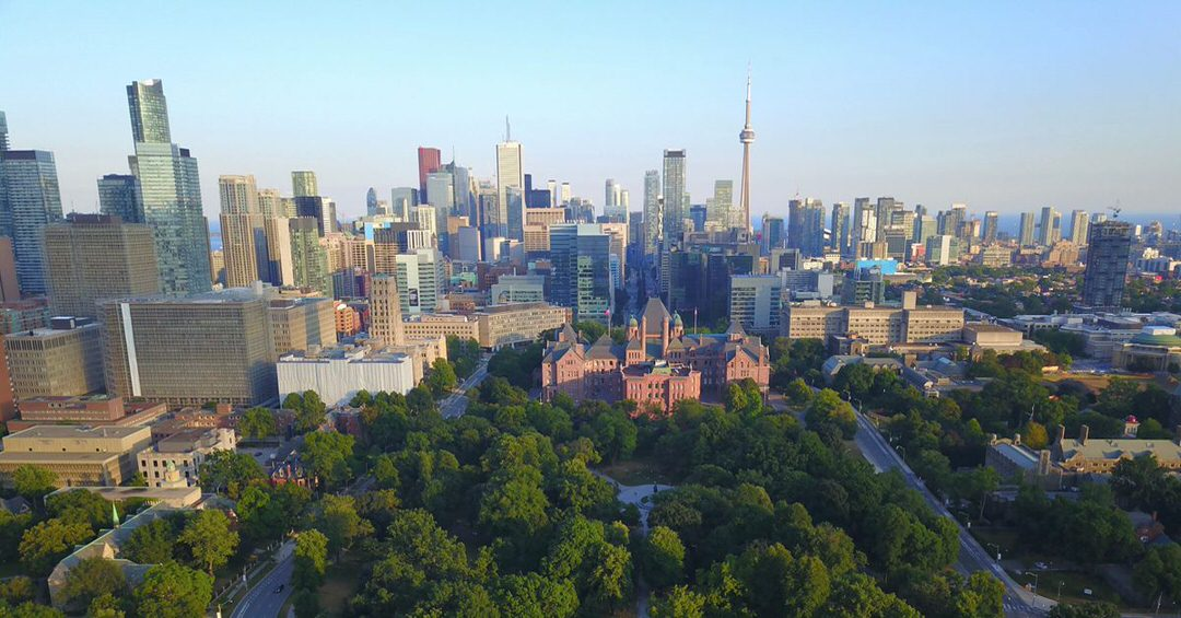Trees surround Queen's Park with tall buildings in the background, including the CN Tower.