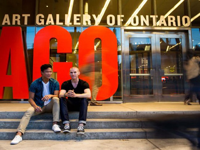 Two men sit on the steps in front of the AGO