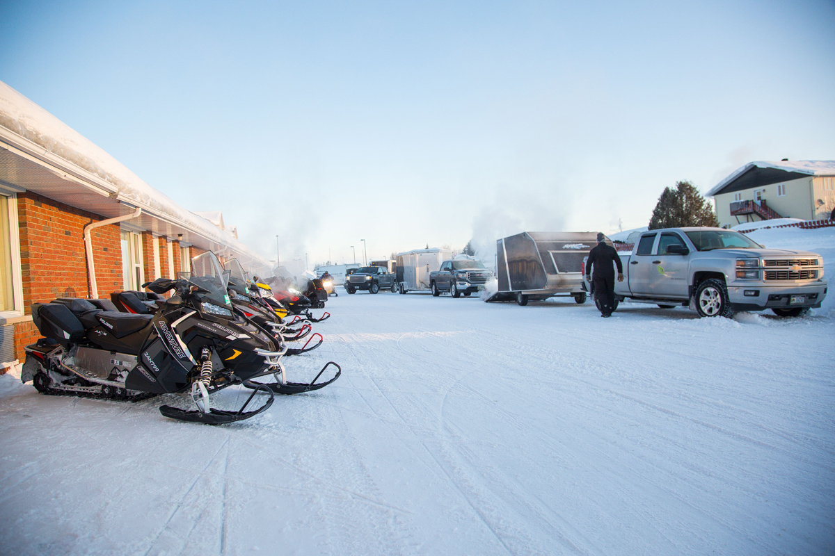 Pickup trucks and motorcycles parked in a snow-covered motel parking lot