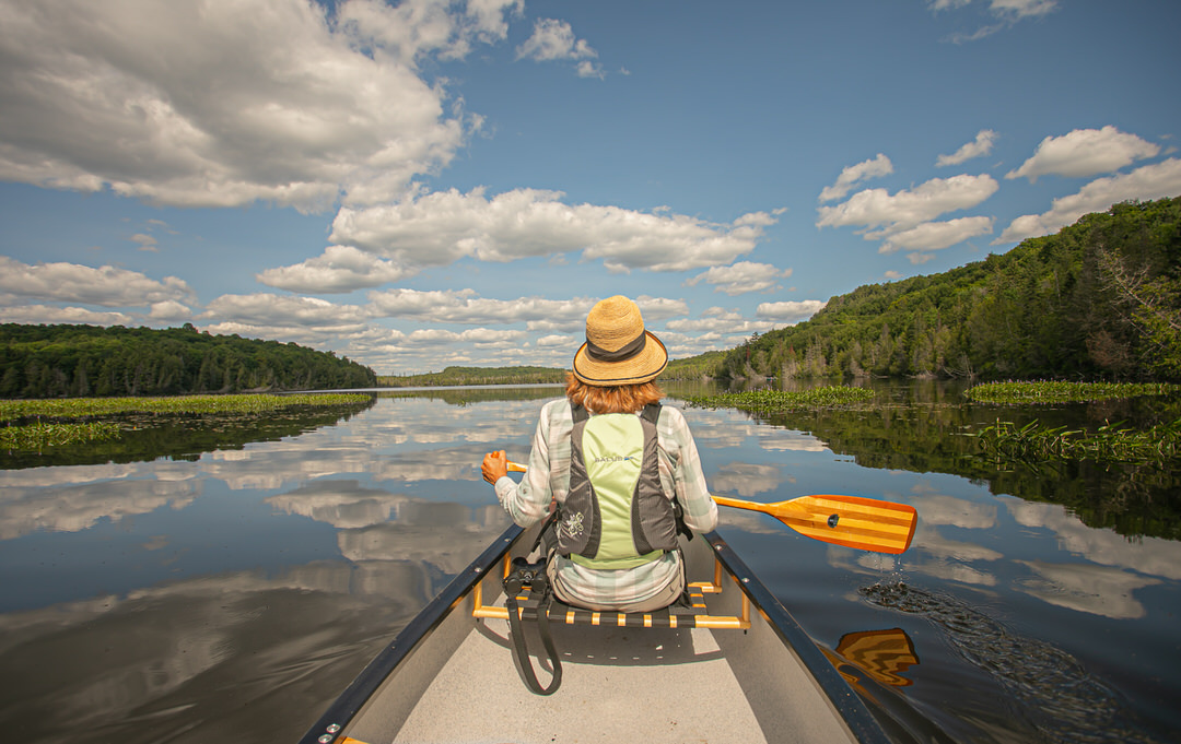 A woman in a canoe paddles across a calm lake
