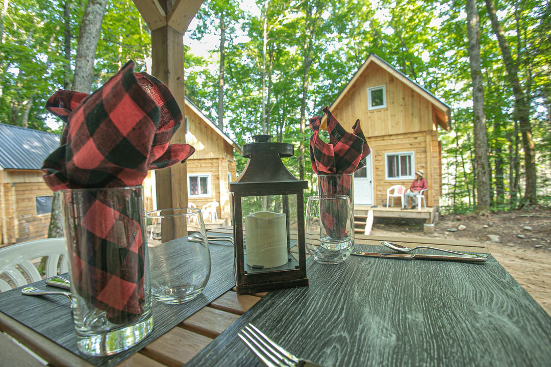 View of three tiny cabins from an outdoor dining table