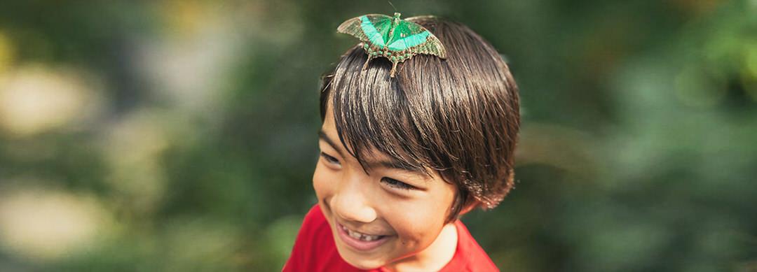 Un garçon avec un sourire sur son visage parce qu'un papillon s'est posé sur sa tête