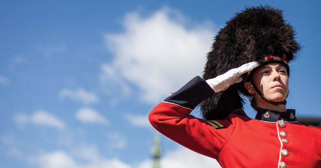 A Mountie saluting in front of the parliament building.