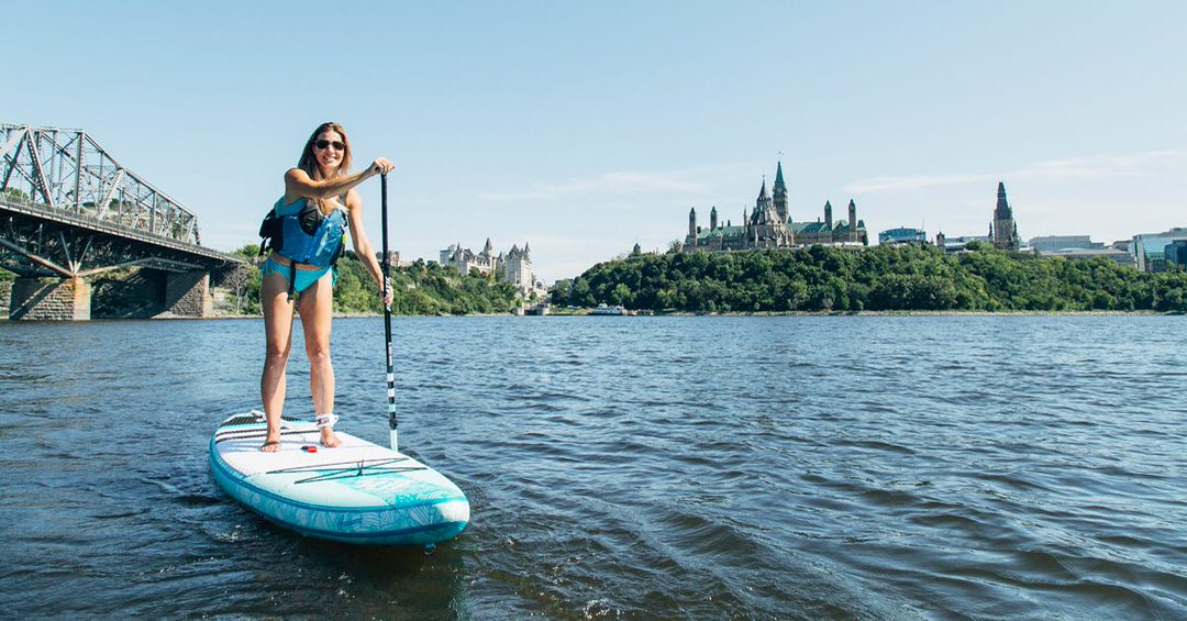 A woman is paddle boarding on the water, leaving behind the Parliament buildings on top the hill.