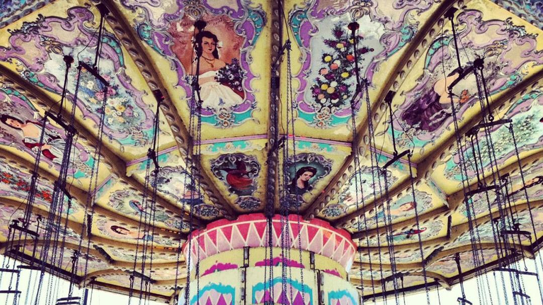 A pastel coloured merry-go-round sits still