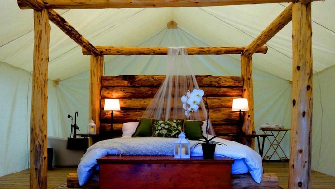 Lit à baldaquin à colonnes de bois au milieu d'une grande tente blanche.