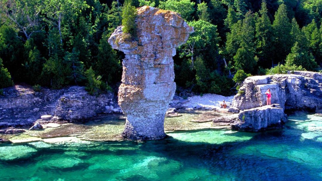 A pillar of rock rises out of clear blue waters on the shores of a forest beyond.