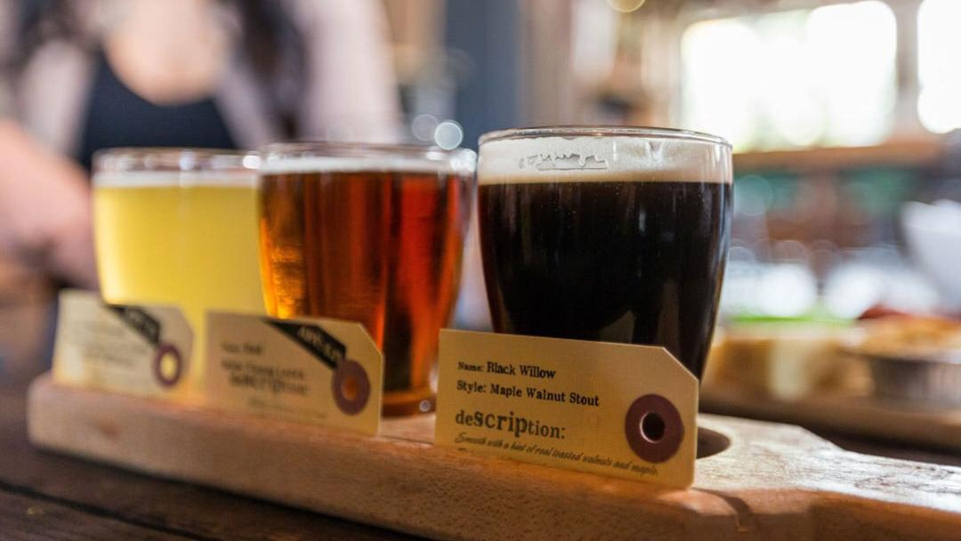 A flight of beer rests on a table