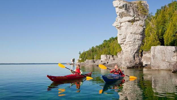 Two women paddling kayaks on a beautiful day