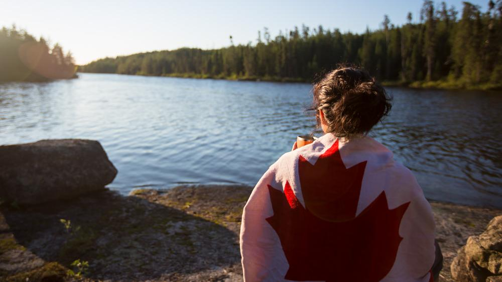 A girl wrapped in a towel with the Canadian Flag sits to admire a beautiful lake