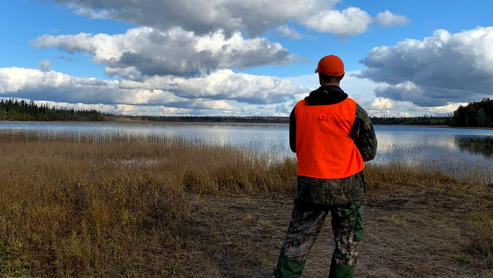 A man wearing a hunter orange vest and cap looks out towards a lake