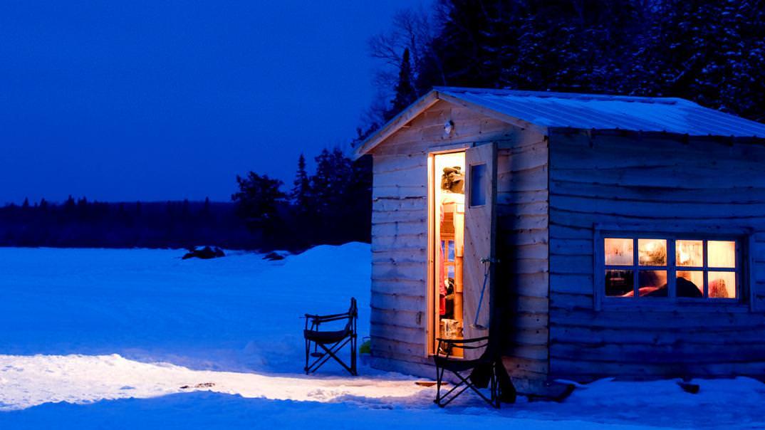 The light from an ice fishing hut illuminates the night