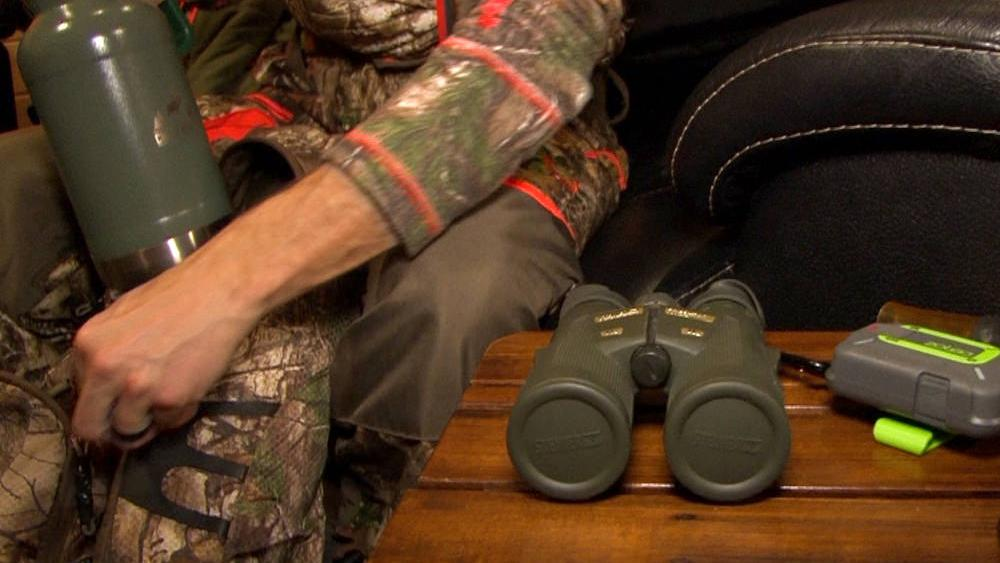 A man dressed in camouflage packs binoculars, a thermos and other hunting gear