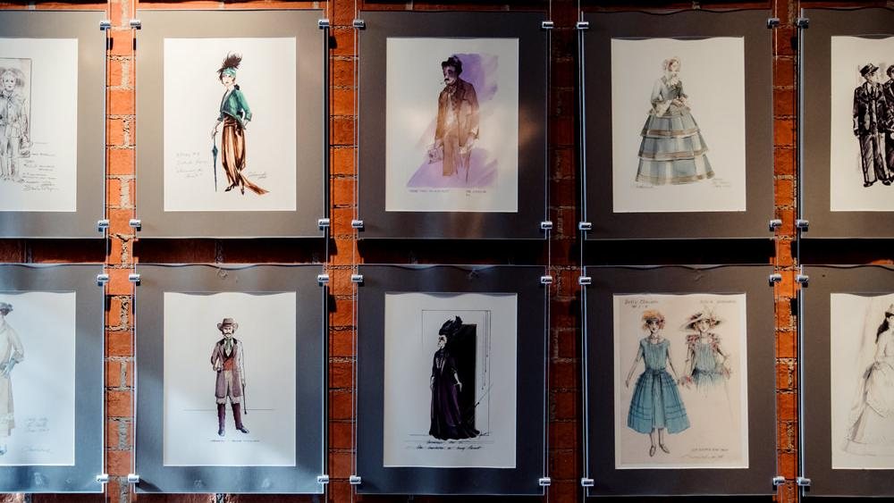 Drawings of theatre costumes fill a wall at the Shaw Festival
