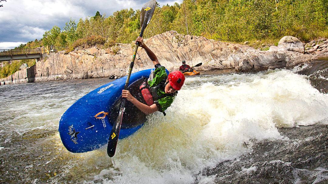 A man in a blue sport kayak rides a rough wave