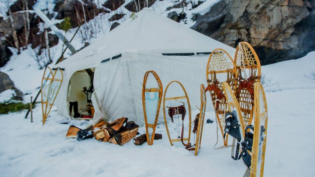 Raquettes à l'extérieur d'une tente pendant l'hiver