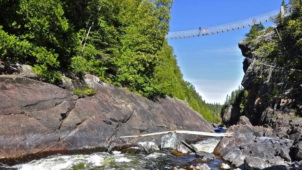 3 people emerge from a walking trail in a forest onto a suspension bridge, overlooking rocks and a stream.