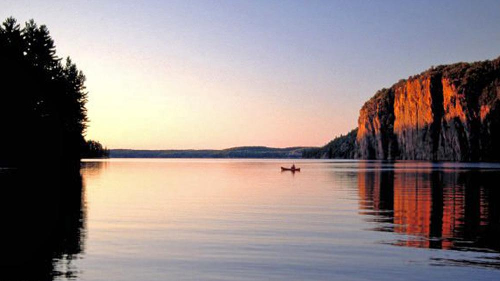 One canoer paddles past a vast cliff on a calm lake at sunset