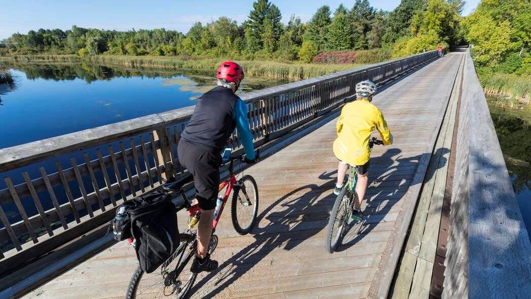 2 people cycling on a wooden bridge with water beneath it, heading to a trail amongst the forest.