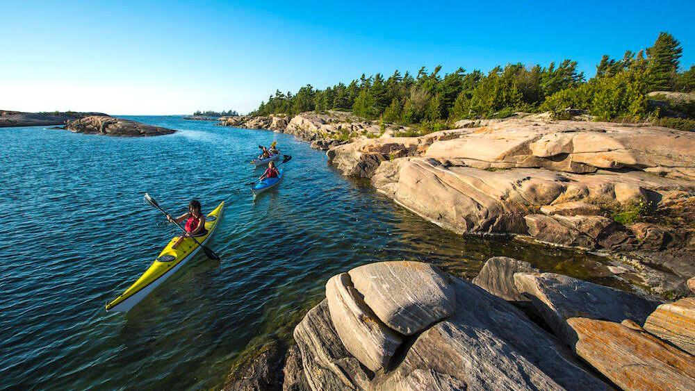 3 people paddling along the lake close to rocky land with trees.