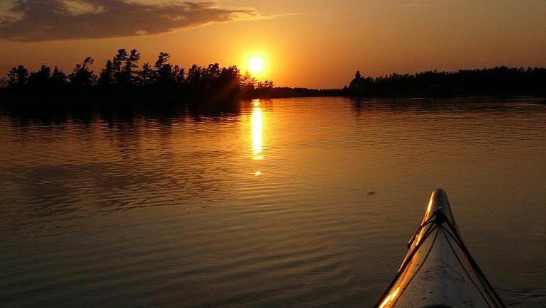 The tip from a kayak shows, as a sunset beams between trees and reflects on the water.