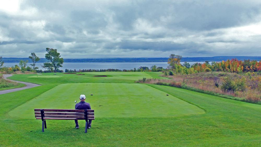 A man sits on a bench overlooking the greens of a golf course