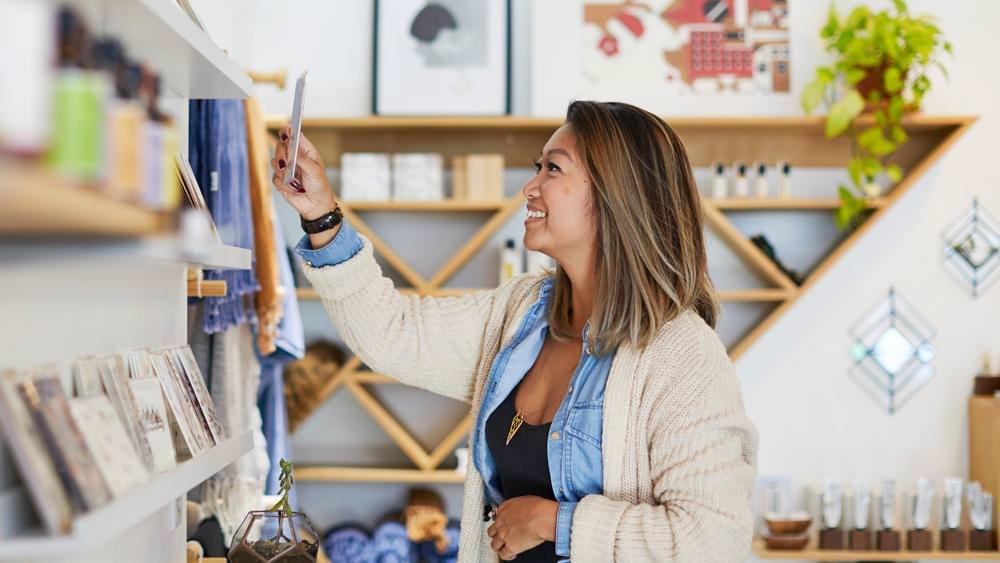 A woman admiring a postcard in a store