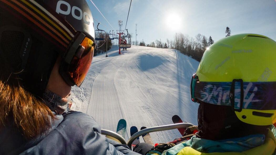 2 people in full down-hill ski gear, riding a ski lift on cold sunny day.