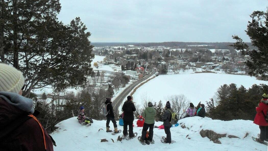 A bunch of people in snowshoe gear on top of a hill, looking at the small town below.