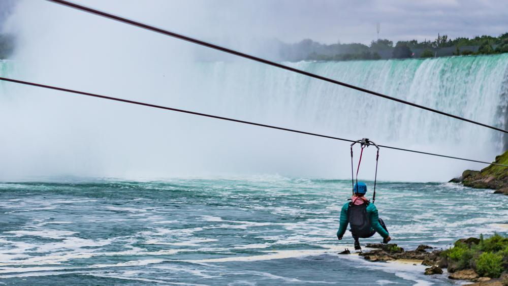 A person rides a zipline in front of the Niagara Falls