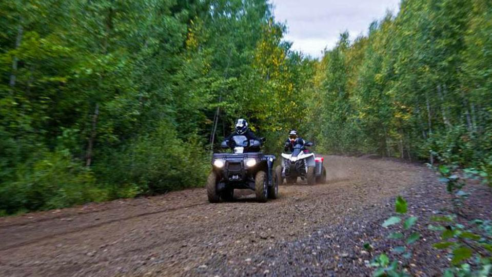 Two people riding ATVs along a gravel road