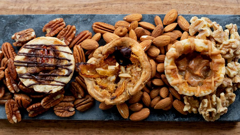 Three delicious butter tarts placed on a charcuterie board surrounded by nuts