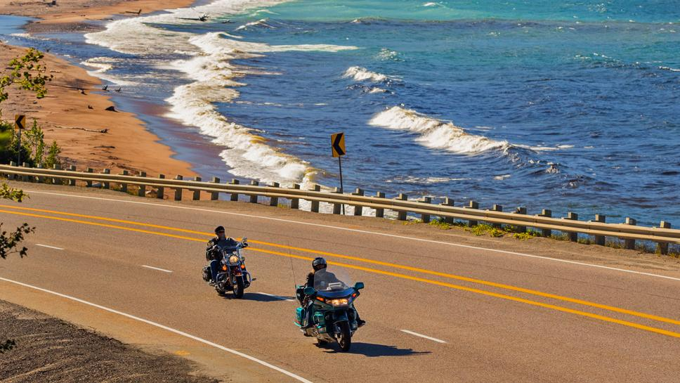 Two motorcyclists ride past a sandy beach