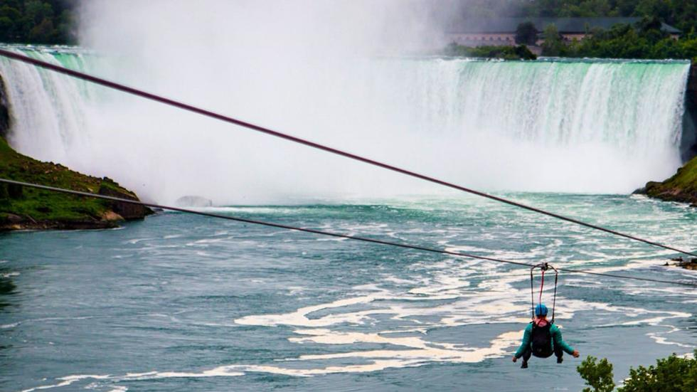 A person zip lining in front of the Niagara Falls