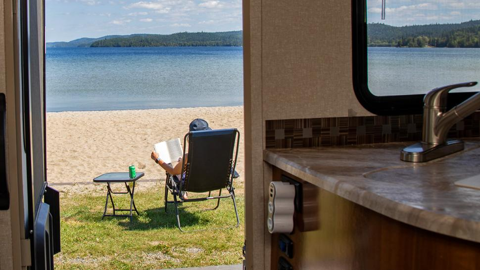 View of a woman sitting on a lawn chair in front of a beach from inside an RV
