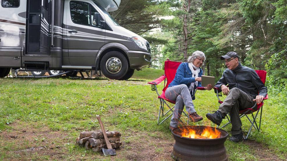 A senior couple enjoying an outdoor campfire near their RV